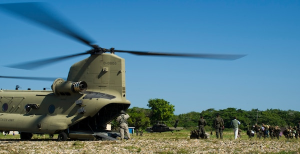 U.S. Army Sgt. David Pressnell, 1-228th Aviation Regiment flight engineer directs Honduran soldiers loading gear and personnel into the back of a U.S. Army CH-47 Chinook Dec. 16, 2015, in the Gracias a Dios Department (state) of Honduras during a troop movement the U.S. provides support to. The two day troop movement is a part of a larger operation called CARAVANA, which the U.S. has supported since October 2014, to assist the Honduran government in disrupting the flow of illicit trafficking through the area. (U.S. Air Force photo by Capt. Christopher Mesnard/Released)