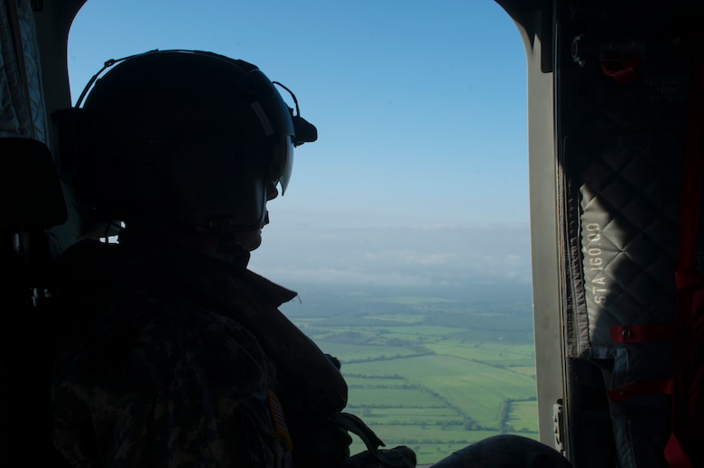 David Uplinger 1-228th Aviation Regiment flight engineer watches the landscape slip by the door of a U.S. Army CH-47 Chinook Dec. 17, 2015, as the aircraft flies over the Gracias a Dios Department (state) of Honduras. The aircraft provided airlift for Honduran troops to help support a request for assistance from the Honduran president in October 2014, to help disrupt the flow of drugs in the region. (U.S. Air Force photo by Capt. Christopher Mesnard/Released)