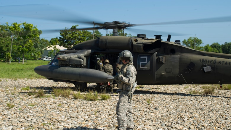 U.S. Army Cpl. Brain McKee, 1-228th Aviation Regiment flight engineer helps Honduran troops load into a U.S. Army UH-60 Blackhawk with their gear Dec. 16, 2015, in the Gracias a Dios Department (state) of Honduras. The mission is a part of the larger Operation CARAVANA, which allows Honduran troops to more easily access areas in the department and better limit the flow of illicit materials and drugs in the area. (U.S. Air Force photo by Capt. Christopher Mesnard/Released)