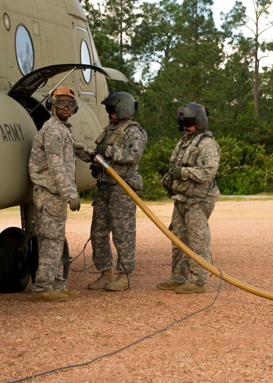 From right, U.S. Army Sgts. David Pressnell and David Uplinger 1-228th Aviation Regiment flight engineers and Spc. Tyree Doyle, Joint Task Force-Bravo Petroleum, Oil and Lubricant specialist refuel a U.S. Army CH-47 Chinook Dec. 17, 2015 at Mocoron Airfield in the Gracias a Dios Department (state) of Honduras. The airfield provides the flying forces a hub to refuel at and embark from when conducting CARAVANA troop movements in the area. The troop movements are part of a combined U.S. and Honduran effort to disrupt the flow of illicit drugs and materials through the region. (U.S. Air Force photo by Capt. Christopher Mesnard/Released)