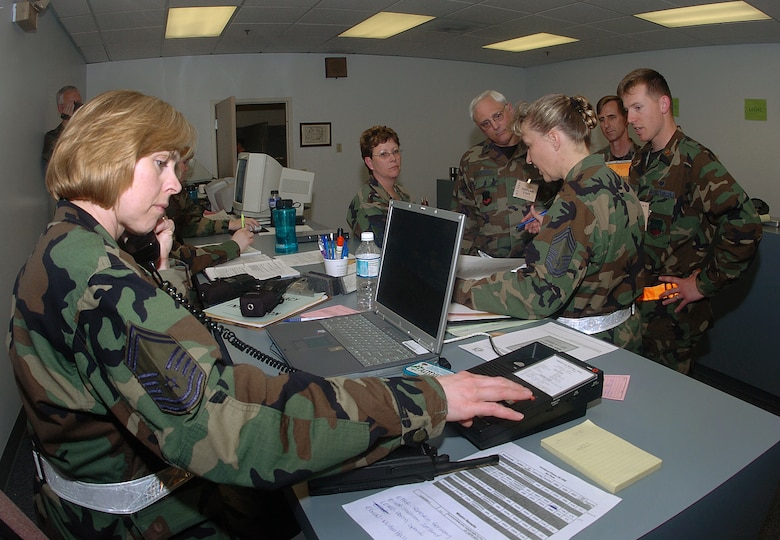 Senior Master Sgt. Jean Allen, assigned to the 142nd Fighter Wing Mission Support Group, left, assist in processing unit personnel during an Operational Readiness Exercise, June 4, 2006, Portland Air National Guard Base, Ore.  Allen retired with more than 32 years of service on Dec. 22, 2015. (Air National Guard photo by Tech. Sgt. John Hughel, 142nd Fighter Wing Public Affairs)