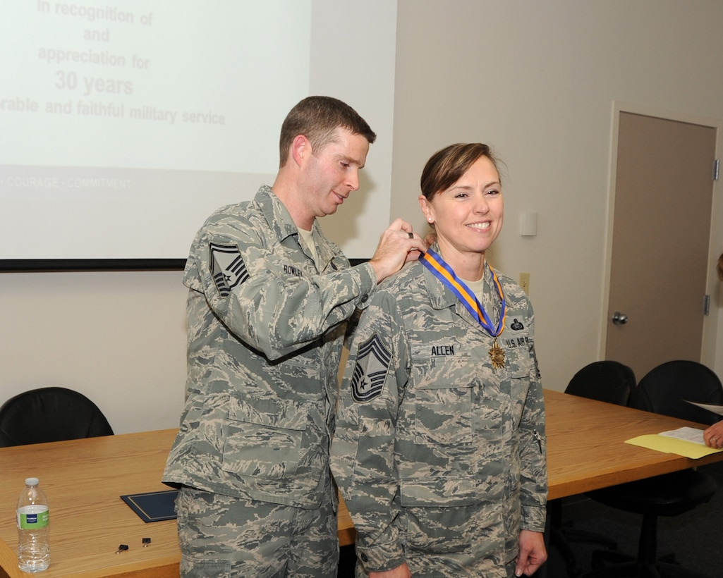In a surprise presentation during Commander's Call, Senior Master Sgt. Brion Rowley presents Chief Master Sgt. Jean Allen with the Oregon National Guard 30-year service medal.  Chief Master Sgt. Allen is the Superintendent for the Force Support Squadron, Portland Air National Guard Base, Ore., Nov. 2, 2013. (Air National Guard photo by Master Sgt. Shelly Davison, 142nd Fighter Wing Public Affairs)