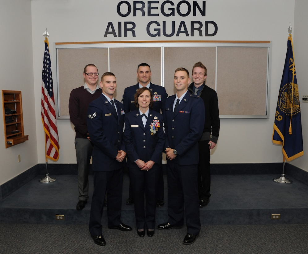 Chief Master Sgt. Jean Allen, center, poses for a photograph with her five sons following her formal retirement ceremony from the Oregon Air National Guard, Dec. 22, 2015, Portland Air National Guard Base, Ore. (Left to right) Jared Ellis, Senior Airman Chris Anderson, Senior Master Sgt. Jason Anderson, 2nd Lt. Jake Anderson and Logan Ellis. (Air National Guard photo by Tech. Sgt. John Hughel, 142nd Fighter Wing Public Affairs)