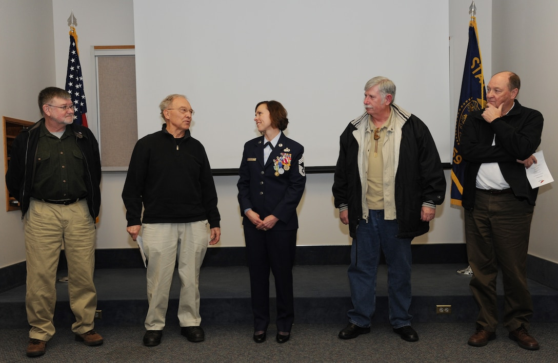 Four retired Oregon Air National Guard Chief Master Sergeants take turns highlighting Chief Master Sgt. Jean Allen, center, career in the Oregon Air National Guard, during her formal retirement ceremony, Dec. 22, 2015, Portland Air National Guard Base, Ore. (Air National Guard photo by Tech. Sgt. John Hughel, 142nd Fighter Wing Public Affairs)