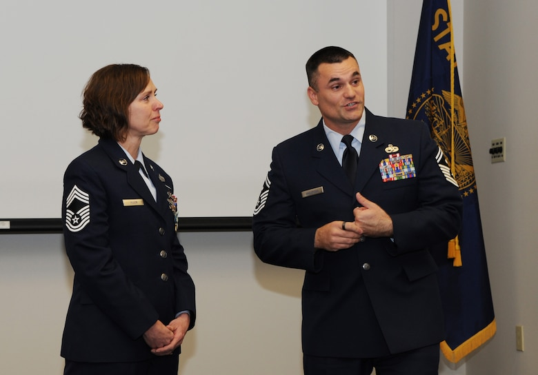 Chief Master Sgt. Jean Allen, left, listens to her son, Air Force Senior Master Sgt. Jason Anderson, right, address those attending her retirement ceremony, Dec. 22, 2015, Portland Air National Guard Base, Ore. (Air National Guard photo by Tech. Sgt. John Hughel, 142nd Fighter Wing Public Affairs)