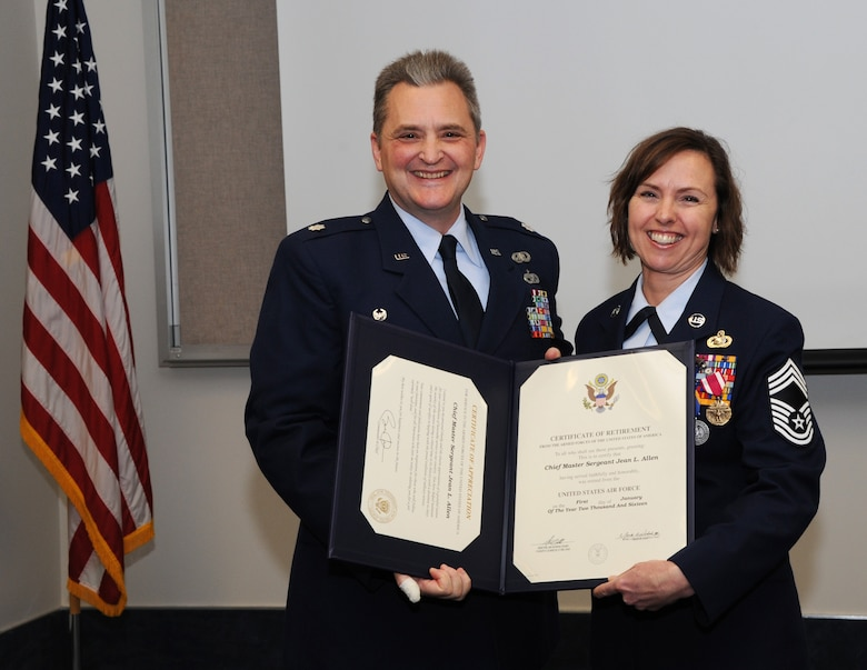 Oregon Air National Guard Lt. Col. Anthony Victoria, 142nd Fighter Wing Force Support Squadron commander, left, presents The Certificate of Retirement from the United States Air Force to Chief Master Sgt. Jean Allen, right, during her formal retirement ceremony from the Air National Guard, Dec. 22, 2015, Portland Air National Guard Base, Ore. (Air National Guard photo by Tech. Sgt. John Hughel, 142nd Fighter Wing Public Affairs)