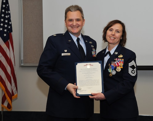 Oregon Air National Guard Lt. Col. Anthony Victoria, 142nd Fighter Wing Force Support Squadron commander, left, presents The Meritorious Service Medal to Chief Master Sgt. Jean Allen, right, during her formal retirement ceremony from the Air National Guard, Dec. 22, 2015, Portland Air National Guard Base, Ore. (Air National Guard photo by Tech. Sgt. John Hughel, 142nd Fighter Wing Public Affairs)