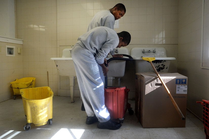 Malachi Ervin, foreground, and Tarvaress Williams, both cadets at the Maryland National Guard's Freestate ChalleNGe Academy, fill a bucket with hot water while stripping and waxing the floors in the academy's barracks building, Nov. 17, 2015. Those at the academy learn not only academic skills in preparation for earning either their GED certificate or high school diploma, but also life skills as well. Rather than simply assigning housekeeping duties to cadets, at the Freestate Academy cadets must formally apply and interview with academy staff as a way to prepare them for job interviews.