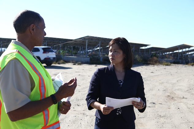 Ms. Christine Harada, Chief of Federal Sustainability Officer, right, receives a brief from Mr. Charles Howell, left, on renewable energy using Marine Corps Camp Pendleton's Solar Photovoltaic System at Box Canyon, aboard Camp Pendleton, Calif., Dec. 29, 2015. The purpose of the visit was to provide the new White House Federal Chief Sustainability Officer information and background regarding Marine Corps Installations West-Marine Corps Base Camp Pendleton's electric vehicle procurement, renewable energy, and how water sustainability programs support the Untied States Marine Corps mission and readiness. (U.S. Marine Corps Photo by Gunnery Sgt. Evan P. Ahlin/Released)
