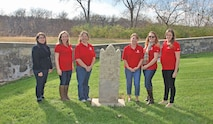 Members of the Historic and Archaeological Society of Fort Riley and Teresa de la Garza, historic architect and cultural resources manager of the Department of Public Works stand with the tombstone that was repaired thanks to donations from HASFR members.  The tombstone of Mary E.E. Cummings was damaged due to natural conditions and needed repairs.  It was brought to the attention of members by de la Garza.  The members contacted Matt Murray, Department of Public Works, to start the process of preservation for the tombstone and the history it symbolized on Fort Riley.  The tombstone has been here almost since the establishment of Fort Riley.  Cumming passed away during the first of two cholera outbreaks on post.
