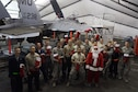 """Members of the 380th Expeditionary Maintenance Squadron enjoy a visit from Santa, played by Chief Master Sgt. William, who handed out filled stockings to the troops at an undisclosed location in Southwest Asia on Christmas. When he's not deployed, """"Santa"""" makes his home at the 916th Air Refueling Wing, Seymour Johnson Air Force Base, North Carolina. (U.S. Air Force/courtesy photo)"""