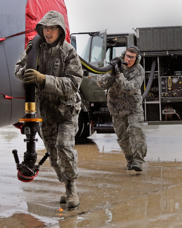 Staff Sgt. Daniel Vergun, 127th Logistics Readiness Squadron fuels technician, and Staff Sgt. Jesse Torma, 191st Maintenance Squadron crew chief, carry the fuel hose to a KC-135 Stratotanker on the flightline at Selfridge Air National Guard Base, Mich., July 9, 2015. Fully loaded, a KC-135 can hold up to 203,000 pounds of fuel. On a typical day, the average load is around 40,000 pounds or 5,900 gallons of fuel. (U.S. Air National Guard Photo by Senior Airman Ryan Zeski/Released)