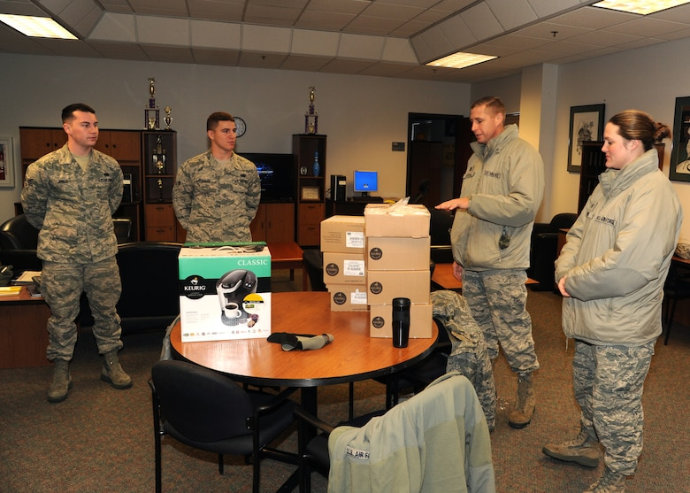 319th Air Base Wing Chaplain (Capt.) Christopher Watson speaks with Airmen from the 319th Logistics Readiness Squadron Dec. 30, 2015, on Grand Forks Air Force Base, North Dakota. Watson and members of the chapel team delivered eight Keurig coffee makers and 10 pallets of Keurig K-cups that were donated to Grand Forks AFB to different units. (U.S. Air Force photo by Airman 1st Class Ryan Sparks/Released)