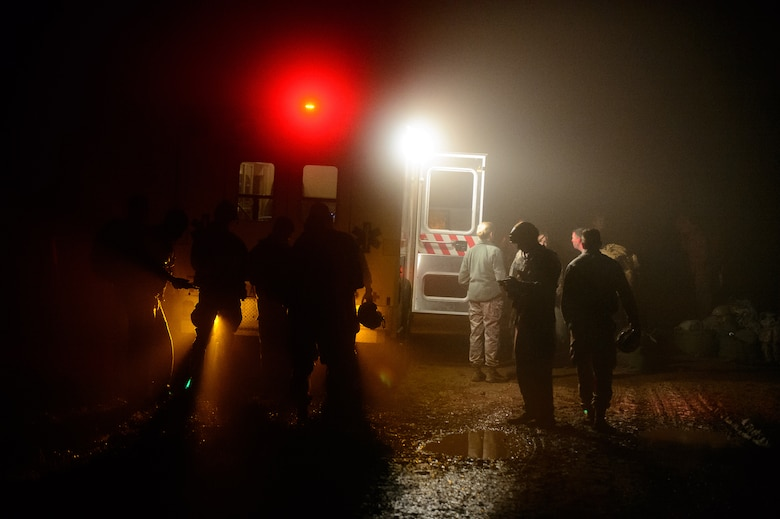 Members of the 435th Air Ground Operations Wing gather near an ambulance during a nighttime training jump Dec. 18, 2015, at Alzey Drop Zone, Germany. Medics from the 435th AGOW waited for their fellow Airmen who dropped with paratroopers in case of an emergency. (U.S. Air Force photo/Staff Sgt. Armando A. Schwier-Morales)