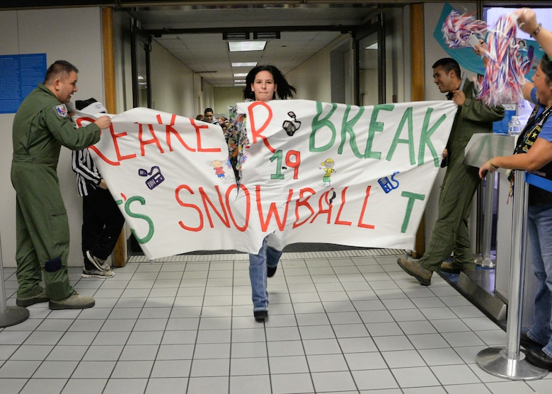 U.S. Air Force Senior Master Sgt. Robert Merrill and Tech. Sgt. Gabriel Garcia Diaz, both flight engineers assigned to the 136th Operations Group, Texas Air National Guard from Naval Air Station Fort Worth Joint Reserve Base, Texas, hold a paper banner for arriving Snowball Express attendees at Dallas-Fort Worth Airport, Dec. 12, 2015. Snowball Express is an organization dedicated to the children of military members who have died while on active duty since Sept. 11. (Air National Guard photo by Tech. Sgt. Vanessa Reed/released)