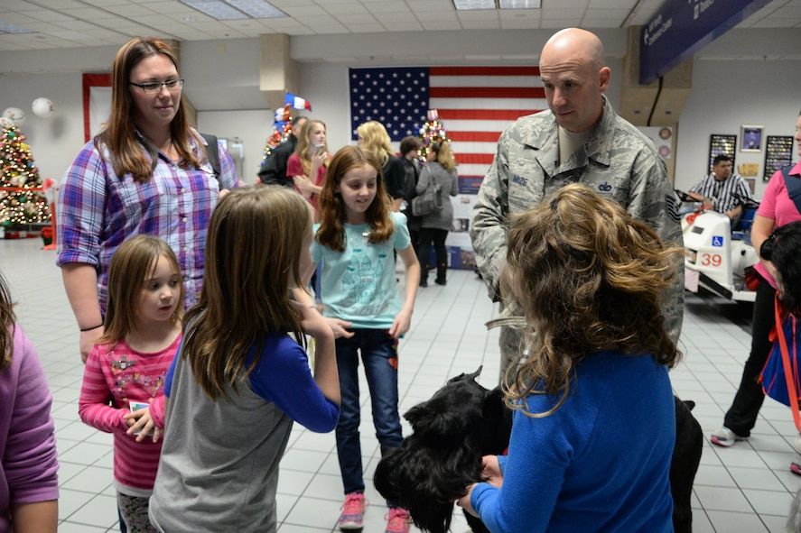 U.S. Air Force Tech. Sgt. Mark Mize, a squad leader from the 136th Security Forces Squadron, Texas Air National Guard from Naval Air Station Fort Worth Joint Reserve Base, Texas, and his therapy dog, Sully, welcome families arriving for Snowball Express 2015 at Dallas-Fort Worth Airport, Dec. 12, 2015. Snowball Express is an organization dedicated to the children of military members who have died while on active duty since Sept. 11. (Air National Guard photo by Tech. Sgt. Vanessa Reed/released)