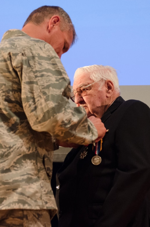 George J. Merz is presented with the French Legion of Honor by Col. Barry D. Gorter, commander of the Kentucky Air National Guard's 123rd Airlift Wing, during a ceremony at Louisville Male High School in Louisville, Ky., Sept. 13, 2015. Merz earned the honor for his actions as a Pfc. in the U.S. Army during World War II. He saw action in both The Battle of the Bulge and the Allied Forces' D-Day invasion of Europe. (U.S. Air National Guard photo by Senior Airman Joshua Horton)