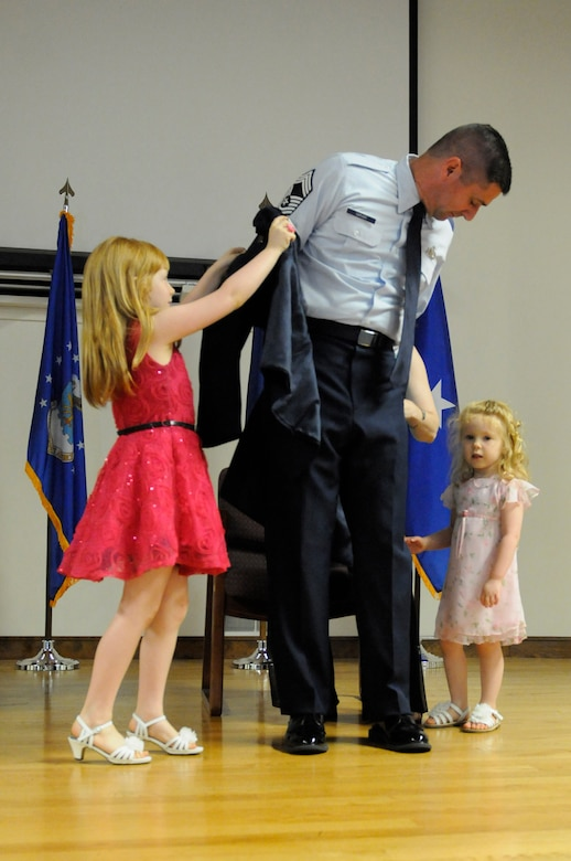Jeffrey A. Sarver is promoted to the rank of chief master sergeant with the help of his family during a ceremony held at the Kentucky Air National Guard Base, Louisville, Ky., June 7, 2015.  Sarver is logistics planner for Joint Forces Headquarters—Kentucky. (U.S. Air National Guard photo by Staff Sgt. Vicky Spesard)