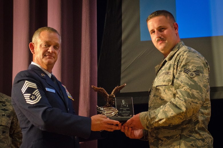 Chief Master Sgt. Brian Pritt (left), air transportation manager for the 130th Logistics Readiness Squadron, presents the Chief Master Sgt. Tommy Downs award to Senior Airman Cory Corbin, an air transportation journeyman in the Kentucky Air National Guard's 123rd Logistics Readiness Squadron, during a ceremony at the Kentucky Air Guard Base in Louisville, Ky., Oct. 13. 2015. The award, named for a former Kentucky Air Guard command chief, is given annually to the top air transportation journeyman in the Air National Guard for excellence in aerial port operations. (U.S Air National Guard photo by Senior Airman Joshua Horton)
