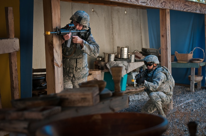 Tech. Sgt. Julien Borchert (left), a squad leader for the Kentucky Air National Guard's 123rd Security Forces Squadron, issues commands during a field training exercise at Ft. Knox, Ky., Oct. 20, 2015. Unit members were being evaluated on their ability to extract a downed pilot from a simulated Afghan village. (Kentucky Air National Guard photo by Master Sgt. Phil Speck)