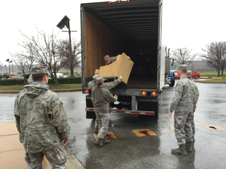 Tech. Sgt. Jared Whitecar, Air Force Mortuary Affairs Operations broadcaster, unloads a chair from a tractor trailer Dec. 23, 2015 at New Castle Air National Guard Base, Del. The furniture was relocated from Dover Air Force Base to create an area for families of the fallen when a dignified transfer was diverted due to weather. (U.S. Air Force photo/Roland Balik)