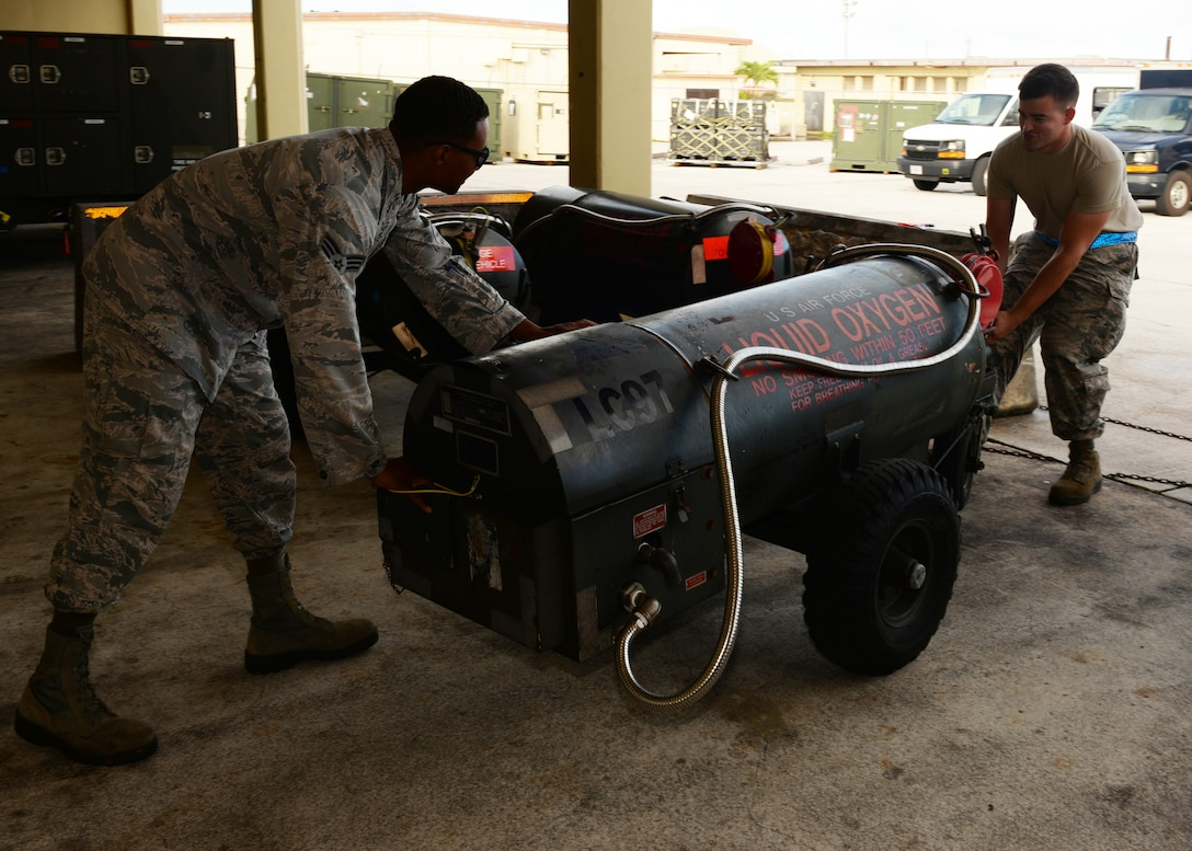Senior Airmen Ferral Ceaser (left) and Kevin Hakala, 36th Maintenance Squadron electrical and environmental technicians, push a liquid oxygen cart for transportation, Dec. 1, 2015, at Andersen Air Force Base, Guam. After inspecting the cart, the team takes the cart to cryogenics to be filled with liquid oxygen. (U.S. Air Force photo/Senior Airman Cierra Presentado)