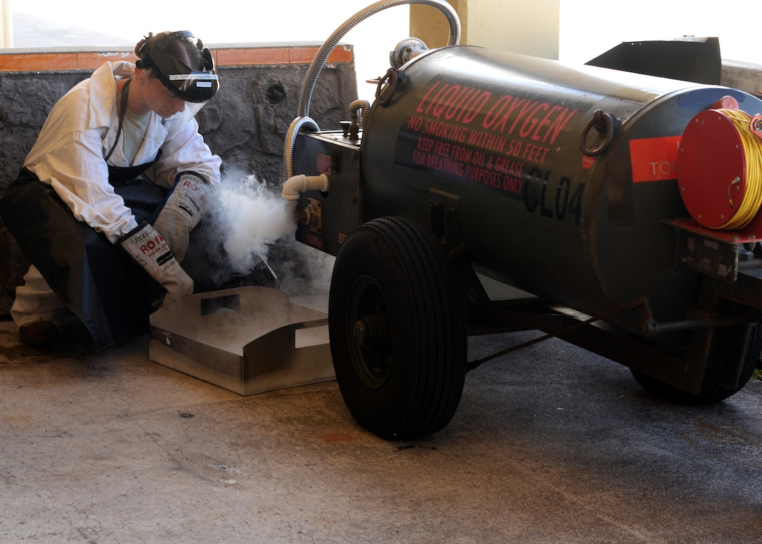 Senior Airman Laenya Maze, 36th Maintenance Squadron, electrical and environmental technician, releases built up pressure from a liquid oxygen cart Dec. 1, 2015 at Andersen Air Force Base, Guam.  On a daily basis, Maze is responsible for inspecting the liquid oxygen carts for discrepancies prior to taking them to the cryogenics shop. (U.S. Air Force photo/Senior Airman Cierra Presentado)