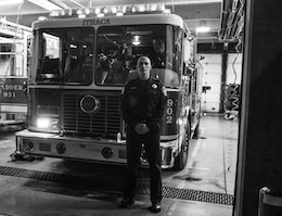 Staff Sgt. Russell Vidler, 98th Training Division (IET) Drill Sergeant of the Year, poses for a picture in front of engine 902 as fellow firefighter Peter Snell peers on Central Station in Ithaca, N.Y., Dec. 18, 2015. Vidler has worked for the city of Ithaca as a firefighter for two years and doubles as a drill sergeant with the Army Reserve. (U.S. Army photo by Sgt. 1st Class Brian Hamilton)