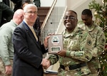 Pat McCormick, left, receives his DLA retirement plaque from DLA Distribution commander Army Brig. Gen. Richard Dix in honor of his 38-year career with the Federal government.