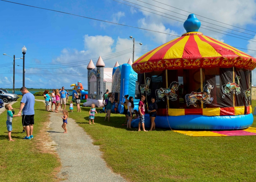 SANTA RITA, Guam (Dec. 19, 2015) Sailors and family members gather around bouncy houses during the first ever Team 15 Day event December 19.  Team 15 Day, hosted by Submarine Squadron 15, is an event that brings together Sailors and families from the submarine community on Guam to educate them on Navy support services and acclimate new arrivals to life on Guam.