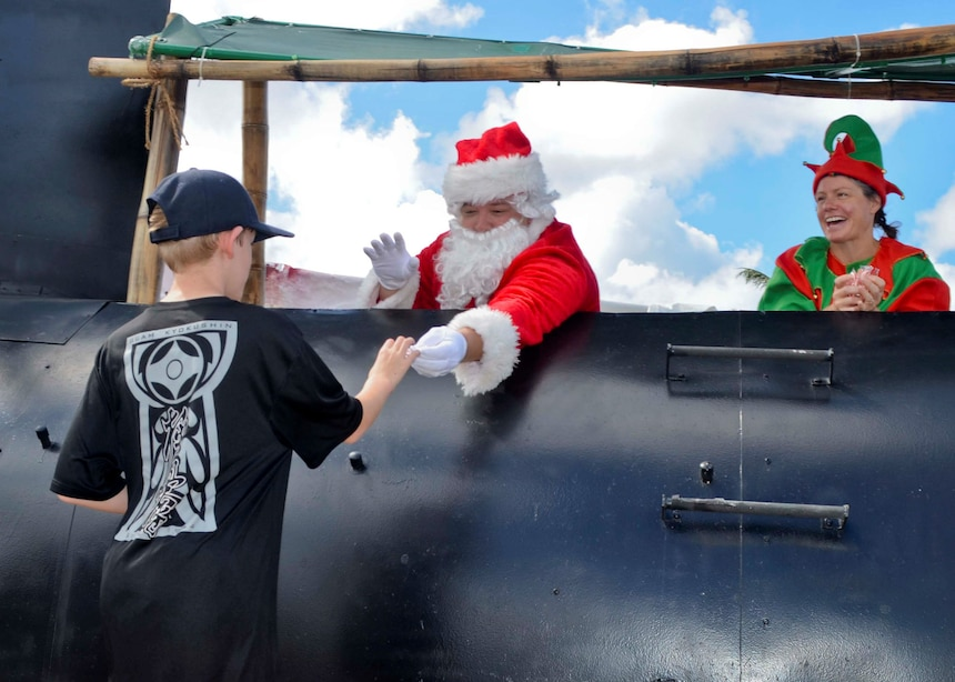 SANTA RITA, Guam (Dec. 19, 2015) A child receives candy from Santa Claus at the first Team 15 Day event December 19.  Team 15 Day, hosted by Submarine Squadron 15, is an event that brings together Sailors and families from the submarine community on Guam to educate them on Navy support services and acclimate new arrivals to life on Guam.