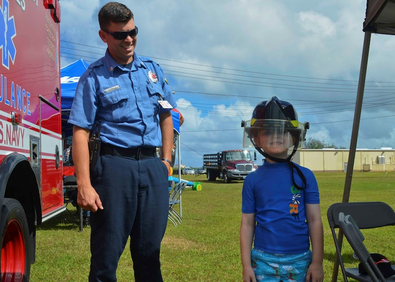 SANTA RITA, Guam (Dec. 19, 2015) Captain Douglas Kelly from the Navy Fire and Emergency Services on Naval Base Guam helps a child dawn a firefighting helmet during the first ever Team 15 Day event December 19.  Team 15 Day, hosted by Submarine Squadron 15, is an event that brings together Sailors and families from the submarine community on Guam to educate them on Navy support services and acclimate new arrivals to life on Guam.