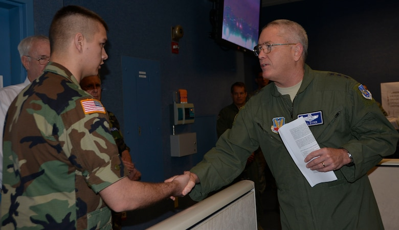 TYNDALL AIR FORCE BASE, Fla. - Lt. Gen. William Etter, Continental  U.S. North American Aerospace Defense Command Region – 1st Air Force (Air Forces Northern) commander, presents his commander's coin for recognition of superior performance to Civil Air Patrol Cadet /Lieutenant Colonel  Alexander English, Central Florida Composite Squadron, during a CAP cadet tour of the 601st Air Operations Center Wednesday.  English is a CAP Bronze Medal of Honor  Recipient who distinguished himself by saving a cadet from imminent harm  when a tornado threatened the camper shelter where the cadet sought refuge. English  ran to the camper and brought the cadet to the safer shelter of a van only minutes before the tornado struck and flipped the camper. English and the other cadets were visiting the 601st AOC as part of their annual week-long winter encampment event designed provide an in-depth orientation to the Civil Air Patrol and the United States Air Force. (Air Force Photo Released/Mary McHale)