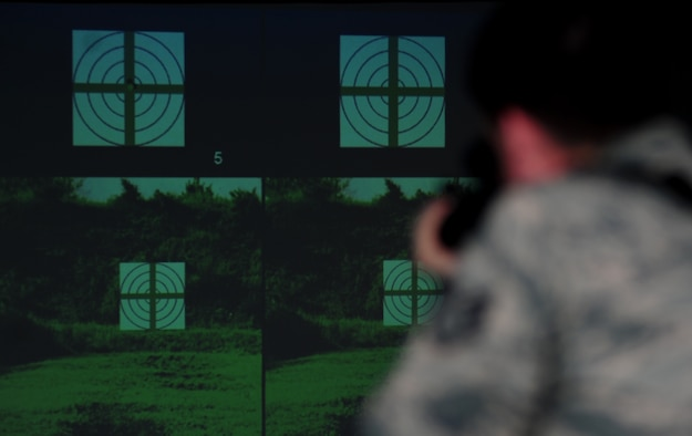 Staff Sgt. Ryan gulley fires at a simulated target Jan. 26, 2015, at Joint Base Langley-Eustis, Va. In addition to realistic scenarios, the new weapons simulator also includes target practice and gives real-time feedback to help improve form and technique. Gulley is a 633rd Security Forces Squadron training instructor. (U.S. Air Force photo/Airman 1st Class Areca T. Wilson)