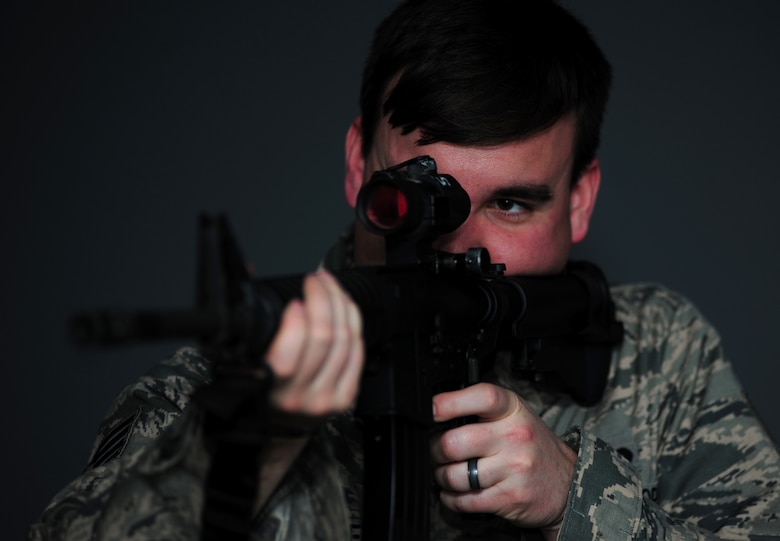 Staff Sgt. Ryan Gulley fires at a simulated target Jan. 26, 2015, at Joint Base Langley-Eustis, Va. The new firearms simulator allows Airmen to gain real-world knowledge and experience through projections of real-life scenarios. Gulley is a 633rd Security Forces Squadron training instructor. (U.S. Air Force photo/Airman 1st Class Areca T. Wilson)