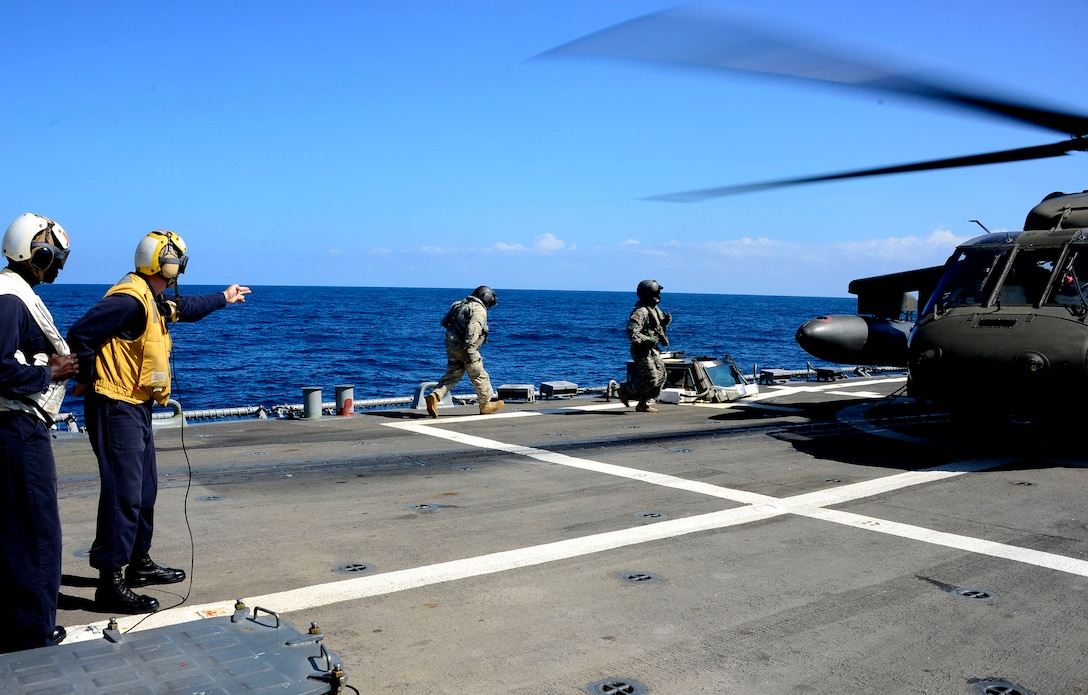 A U.S. Navy aircraft handling officer signals for members of the 1st Battalion, 228th Aviation Regiment to board a UH-60 Blackhawk helicopter during deck landing qualifications off the coast of Honduras, Feb. 1, 2015.  The 1-228th Avn. Reg. aircrew participated in deck landing qualifications on board the USS Kauffman to qualify pilots and crew chiefs on shipboard operations.  Kauffman is on its final scheduled deployment to the U.S. Southern Command area of responsibility supporting multinational, counter-narcotics operation known as Operation Martillo. (U.S. Air Force photo/Tech. Sgt. Heather Redman)