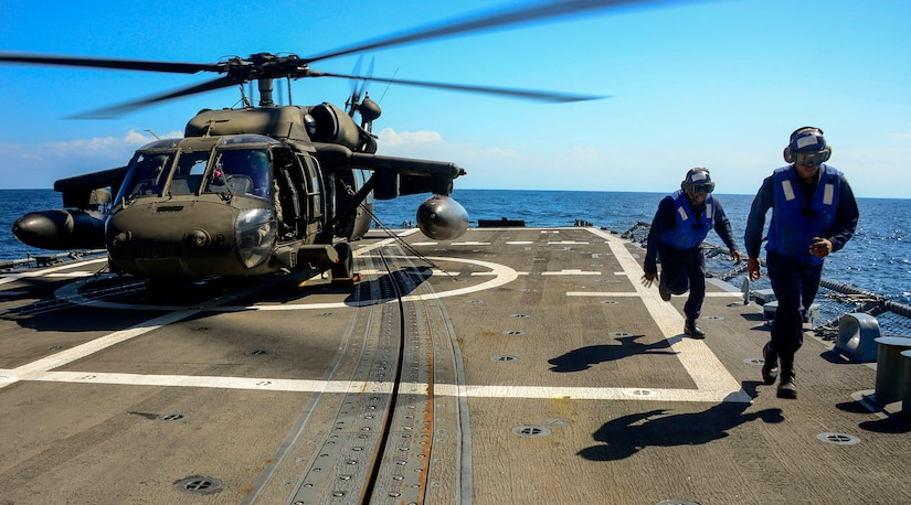 U.S. Navy plane handlers leave the rotor area after tying down a UH-60 Blackhawk helicopter assigned to the 1st Battalion, 228th Aviation Regiment during deck landing qualifications off the coast of Honduras, Feb. 1, 2015.  The 1-228th Avn. Reg. aircrew participated in deck landing qualifications on board the USS Kauffman to qualify pilots and crew chiefs on shipboard operations.  Kauffman is on its final scheduled deployment to the U.S. Southern Command area of responsibility supporting multinational, counter-narcotics operation known as Operation Martillo. (U.S. Air Force photo/Tech. Sgt. Heather Redman)