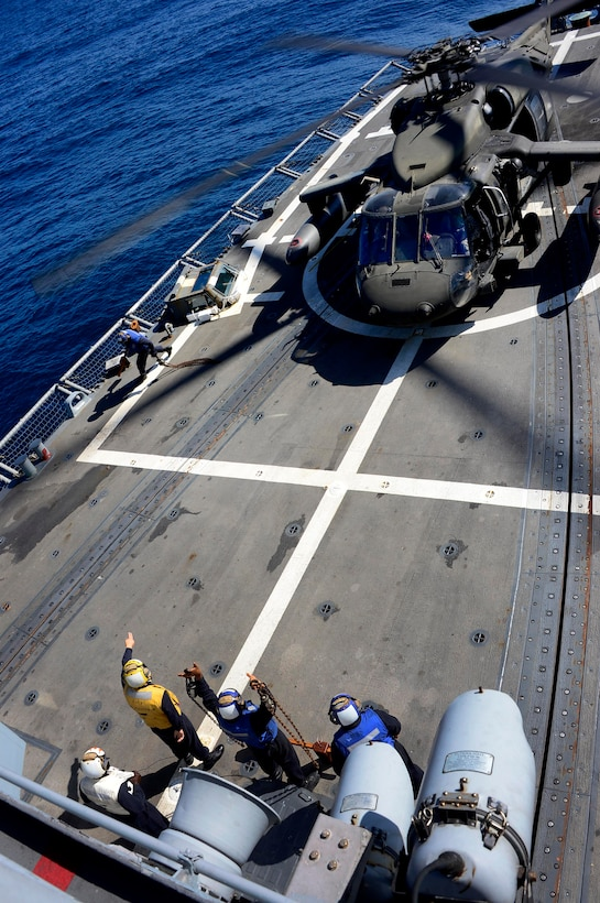 A U.S. Navy aircraft handling officer, assigned to the USS Kauffman, signals to the pilot of a UH-60 Blackhawk helicopter, assigned to the 1st Battalion, 228th Aviation Regiment, that the chalks and ties have be removed and the aircraft can take off during deck landing qualifications off the coast of Honduras, Feb. 1, 2015.  The 1-228th Avn. Reg. aircrew participated in deck landing qualifications on board the Kauffman to qualify pilots and crew chiefs on shipboard operations.  Kauffman is on its final scheduled deployment to the U.S. Southern Command area of responsibility supporting multinational, counter-narcotics operation known as Operation Martillo. (U.S. Air Force photo/Tech. Sgt. Heather Redman)