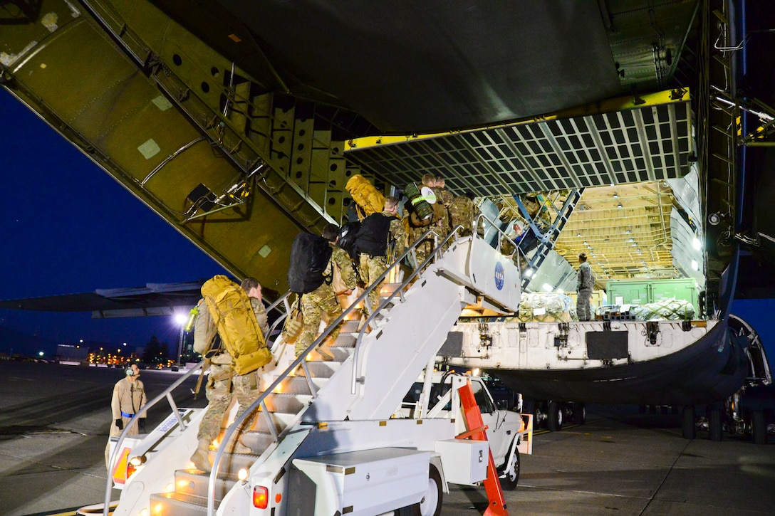 California Air National Guardsmen from the 129th Rescue Wing, Moffett Federal Airfield, Calif., prepare to board a C-5 Galaxy aircraft for their overseas deployment. (U.S. California Air National Guard photo by 1st Lt Roderick Bersamina)