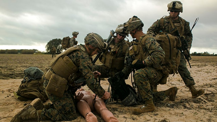 Marines with Special-Purpose Marine Air-Ground Task Force Crisis Response – Africa treat a simulated casualty for a gunshot wound to the leg during an alert-force drill at Rota Air Base, Spain, Jan. 29, 2015. A platoon of Marines secured the casualty and an extraction point nearby as a test of the unit's ability to rapidly respond to regional crises. (U.S. Marine Corps photo by Sgt. Paul Peterson/Released)