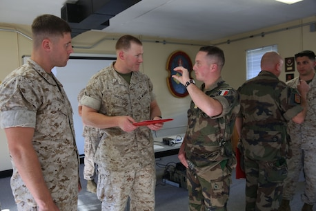 "Captain Daniel F. Burns, a ground intelligence officer for 2nd Bn., 6th Marines, Capt. Kelby Breivogel, an information officer with 2nd Bn., 6th Marines, and Capt. Stephen Castillo, a French officer embedding with 2nd Battalion, 6th Marine Regiment, 2nd Marine Division, talk over future plans for the unit's international exercise, Bold Alligator, during an award ceremony aboard Marine Corps Base Camp Lejeune, Oct. 20, 2014. ""We will accept them into the battalion, they'll partner with us, they'll go on missions with us, and they'll observe our staff planning. We're really going to work hard to integrate them into all of our planning exercises,"" said Lt. Col. James Lively, the commanding officer for 2nd Bn., 6th Marines."