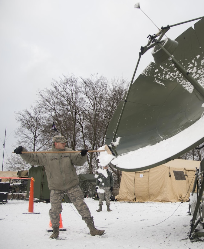 Senior Airman Erik Stauffer cleans snow off of a satellite during exercise Juniper Thunder Jan. 30, 2015, at Ramstein Air Base, Germany. Juniper Thunder aimed to help the interoperability between Air Force and Army combat communications systems. Stauffer is a transmissions systems technician assigned to the 1st Combat Communications Squadron. (U.S. Air Force photo/Senior Airman Jonathan Stefanko)