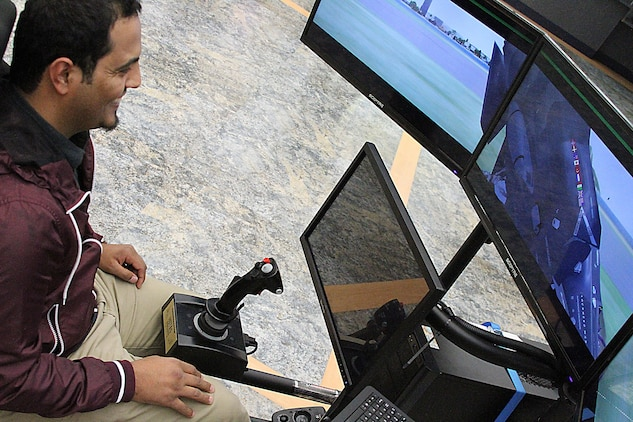 West Virginia University student Abdullah Lasharari, a Saudi Arabia native, flies a 4th Marine Corps District Flight Simulator at a recruiting event, Morgantown, West Virginia Jan. 23, 2015. The program helps identify students who would be interested in an aviation career with the Marines.  (U.S. Marine Corps photo by Cpl. Amber Williams/Released)