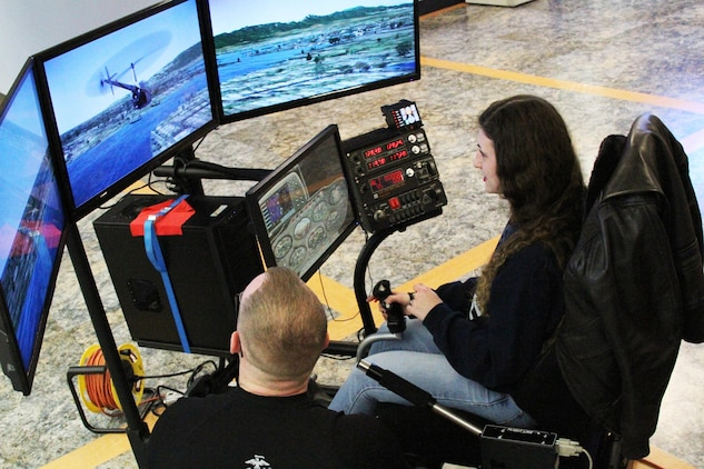 Marine Corps Sgt. Travis Brockman, an Enhanced Area Canvasing recruiter and Campbellsville, Kentucky native, assists a West Virginia University student Darian Seese fly the 4th Marine Corps District Flight Simulator at a recruiting event Jan. 23, 2015 in Morgantown, West Virginia. The program helps expose students to Marine Corps Aviation as a career choice.  (U.S. Marine Corps photo by Cpl. Amber Williams/Released)