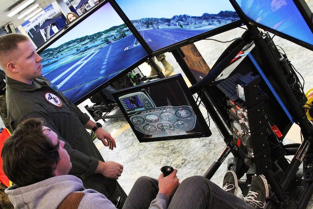 Marine Corps Capt. Richard Jacobs, the aviation assistant for officer procurement and Millville, Pennsylvania native, helps a West Virginia University student fly the 4th Marine Corps District flight simulator at a recruiting event, Jan. 23, 2015 in Morgantown, West Virginia. The program helps identify students who might be interested in an aviation career with the Marines.  (U.S. Marine Corps photo by Cpl. Amber Williams/Released)