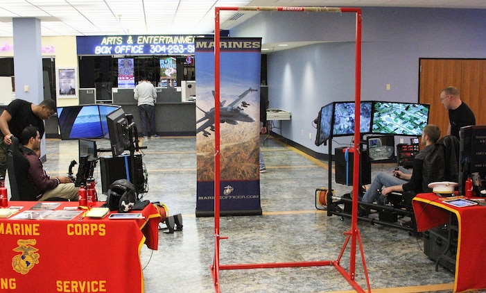 Two students from West Virginia University fly simulators during a recruiting display at West Virginia University Jan. 23, 2015. The 4th Marine Corps District Flight Operation Program, also known as MCFOP, and the Enhanced Marketing Vehicle team, Sgt. Christian Todd (left)and Sgt. Travis Brockman (right) assist Recruiting Station Frederick's Officer Selection Office during an aviation enhanced area canvassing event geared toward aviation recruiting. The new simulators allow Marines to interact with students in a more hands-on environment.   (U.S. Marine Corps photo by Cpl. Amber Williams/Released)