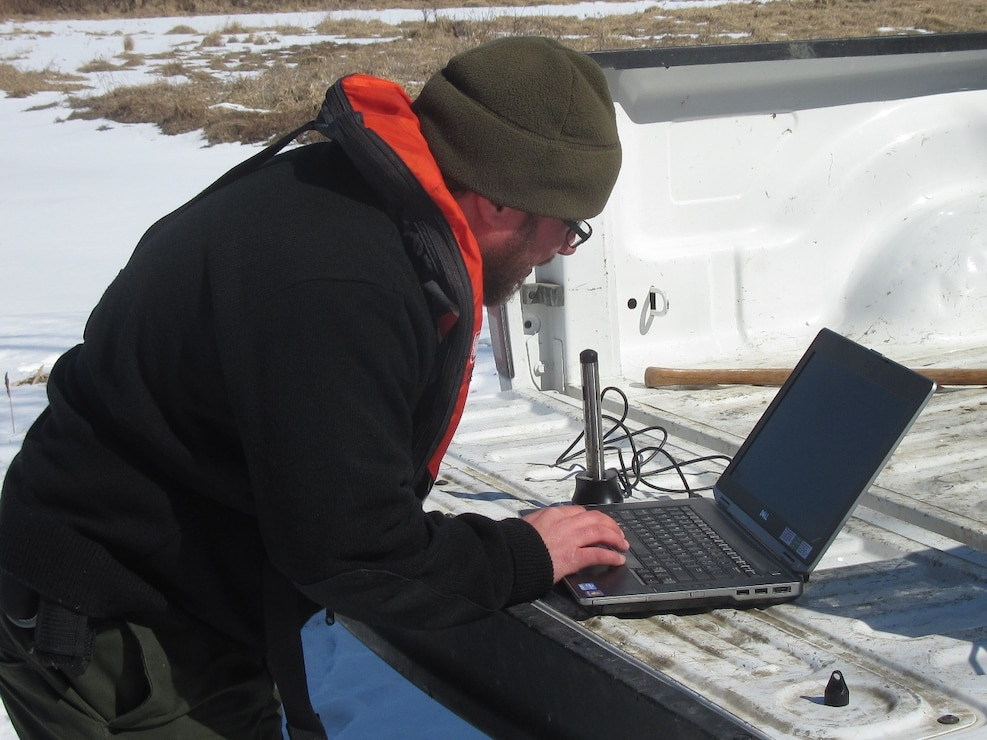 Park Ranger Jason Cote downloads data from a data logger on a tributary to Shenango Lake.