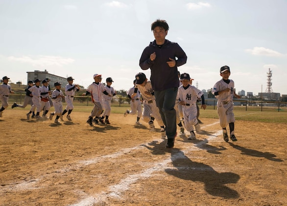 Masahiro Ito leads Japanese and American kids in a cool down run after a game at a baseball clinic Jan. 24 on Camp Kinser. This was the first baseball clinic held on Camp Kinser. Ito is a staff member of the Chicago Cubs.
