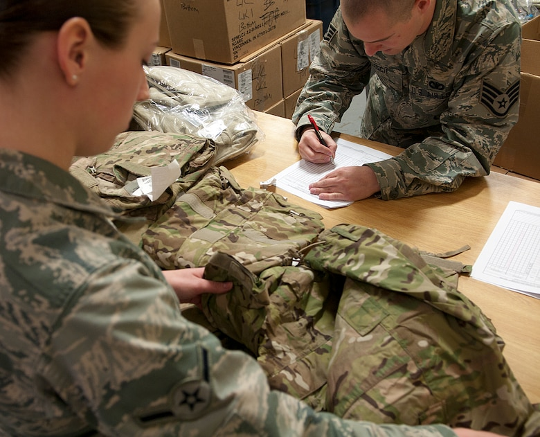 Airman Chelsea Kidman, 790th Missile Security Forces Squadron Security Support Team, inspects her new uniforms as Staff Sgt. Richard Roesch, 90th Security Support Squadron assistant NCO-in-charge of supply, checks the gear off a list Feb. 2, 2015, in the Peacekeeper High Bay on F.E. Warren Air Force Base, Wyo. The new uniform's design helps defenders blend in to the operating environment of F.E. Warren and the missile complex. (U.S. Air Force photo by Airman 1st Class Brandon Valle)