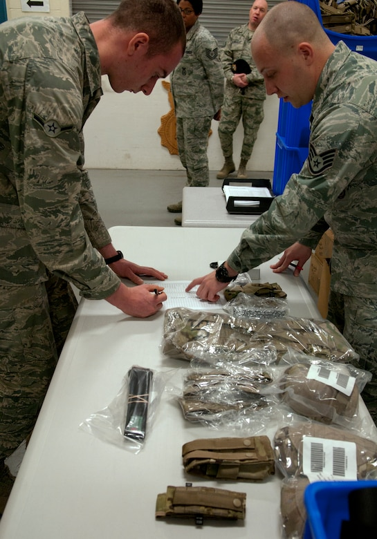 Staff Sgt. Morran, 90th Security Support Squadron assistant NCO-in-charge of mobility, helps Airman Ryan Jones, 790th Missile Security Forces Squadron Security Support Team, check items off the list of new Operation Enduring Freedom Camouflage Pattern gear Feb. 2, 2015, in the Peacekeeper High Bay on F.E. Warren Air Force Base, Wyo. Airmen received new equipment and uniforms as part of the Air Force Global Strike Command Model Defender Program. (U.S. Air Force photo by Airman 1st Class Brandon Valle)
